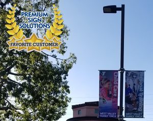 Premium Sign Solutions' Honoring Our Favorite Customers seal over a an outdoor photoraph featuring pole banners made for West Valley YMCA.