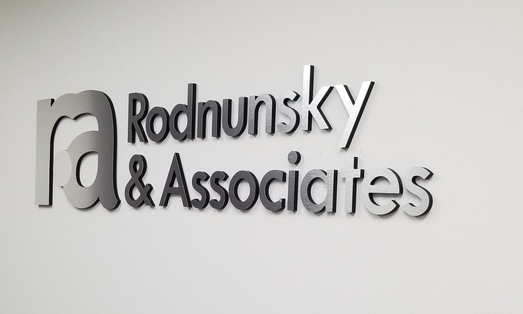 Our law firm lobby sign for Rodnunsky and Associates composed of laser cut black acrylic with brushed metal lettering and polished metal.