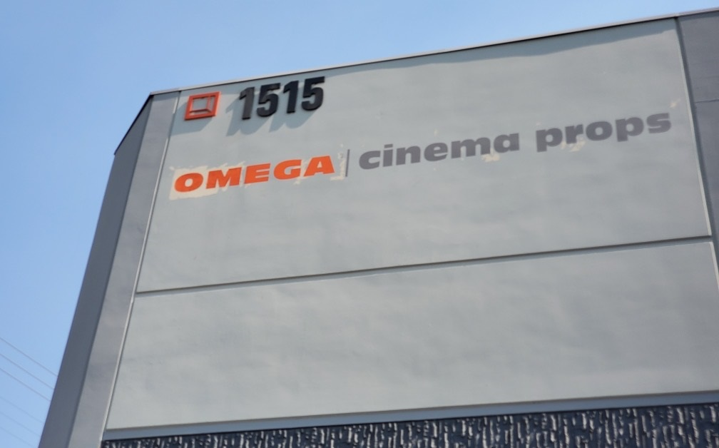 A hand-painted sign is a time tested way to get eyes on your brand like this one for Omega Cinema Props in Los Angeles.