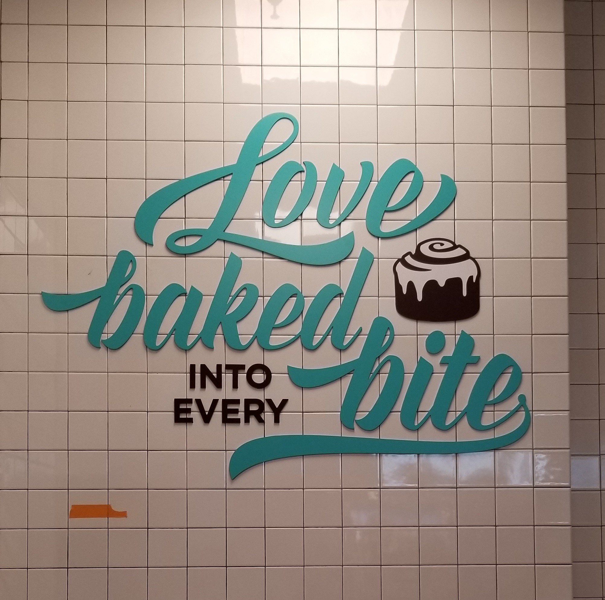 """Cinnabon's new restaurant lobby sign that very cutely tells people that """"Love is Baked Into Every Bite,"""" made in partnership with TubeArt."""