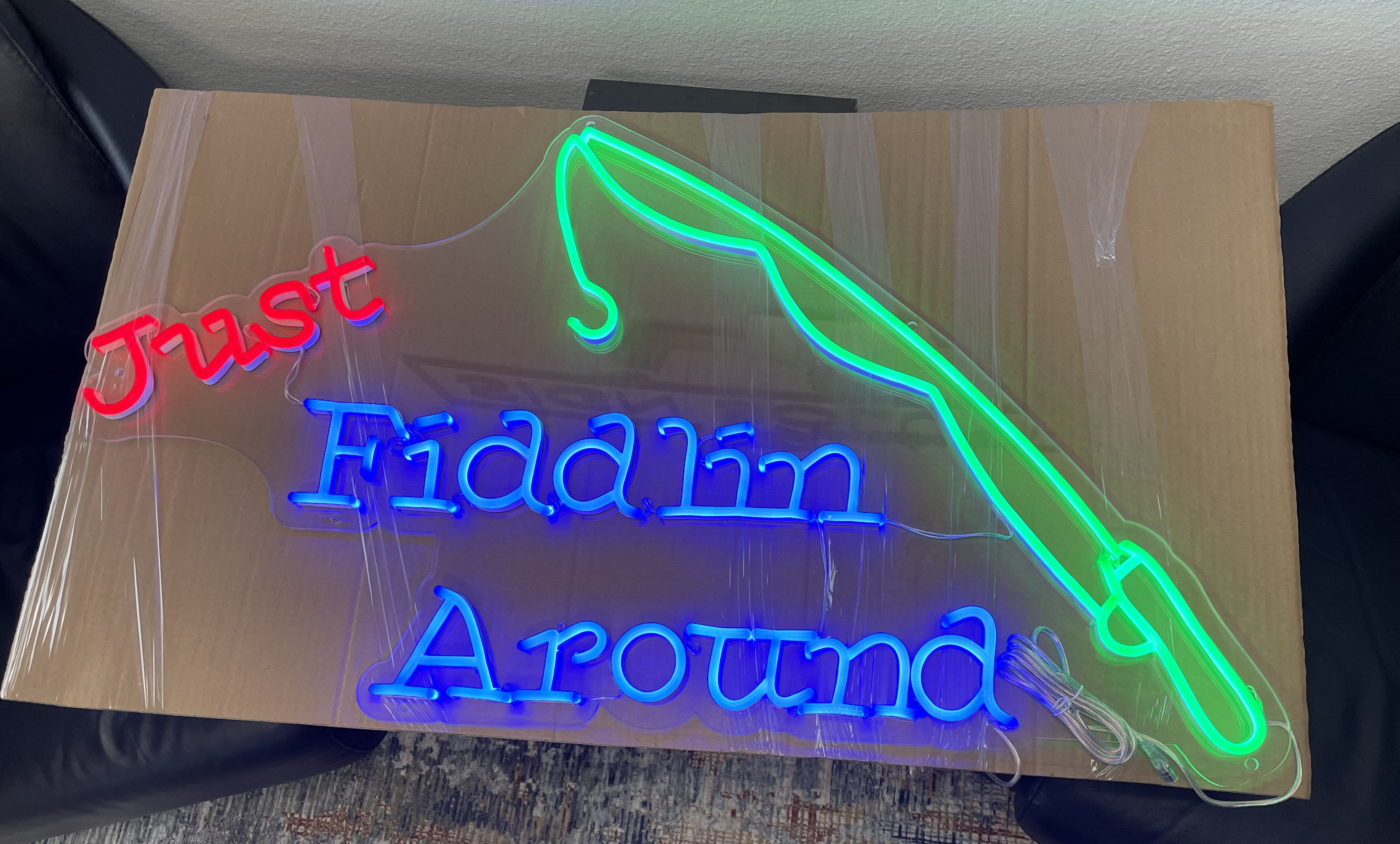 """The holidays are approaching and it's time to decorate places with signage even give them as gifts. Like this neon sign gift spelling out """"Just Fiddlin Around."""""""