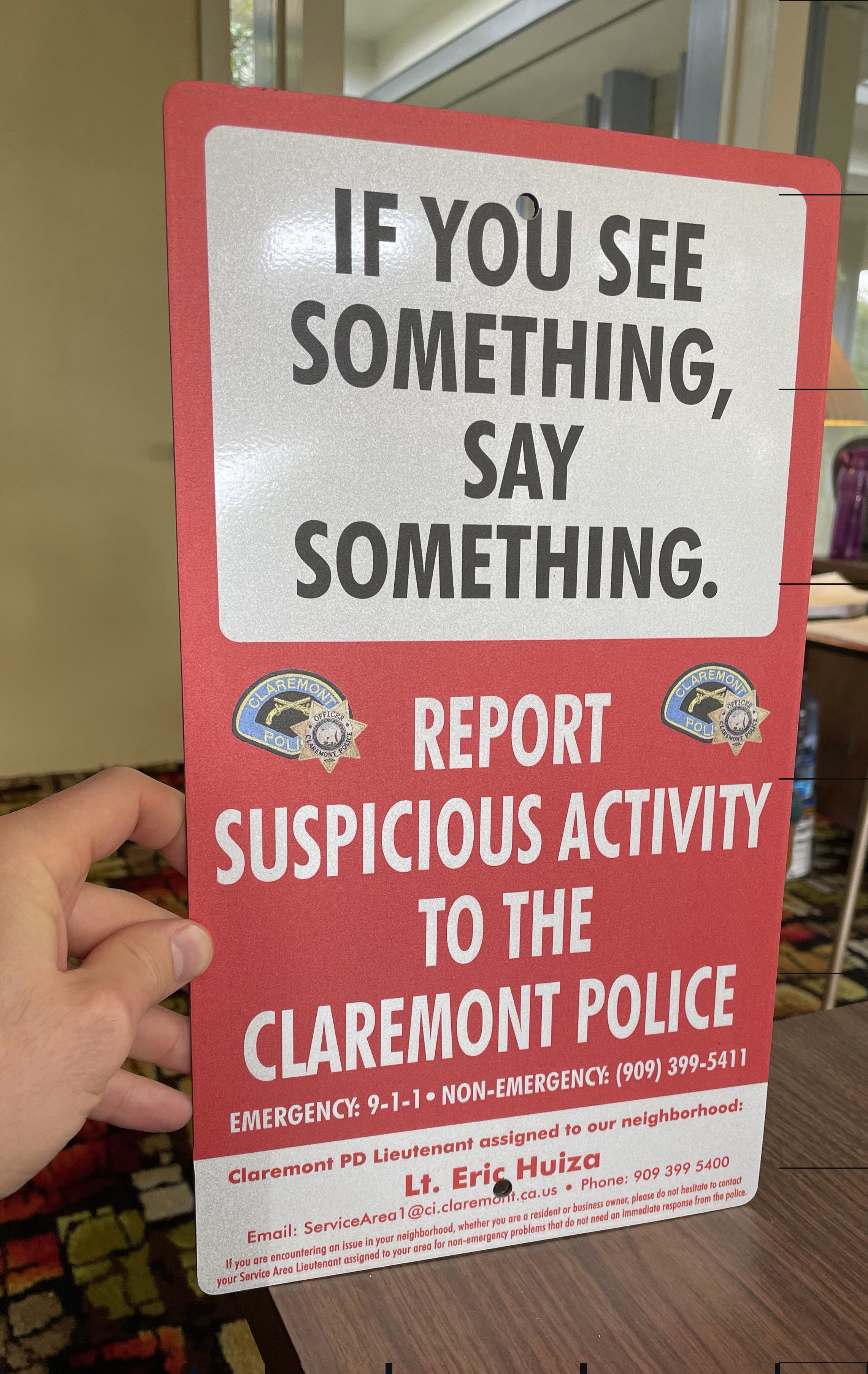 """Parking lot signs for Claremont displaying the words """"See Something Say Something."""" The public safety signs show the contact information of local authorities."""